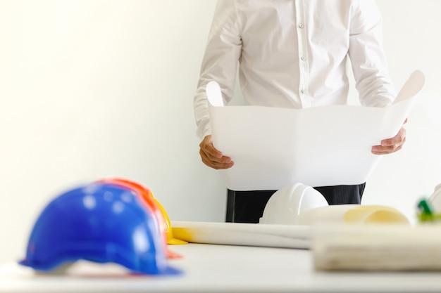 Kask bezpieczeństwa na stole w biurze, inżynier koncepcji pracy zespołowej budownictwa
