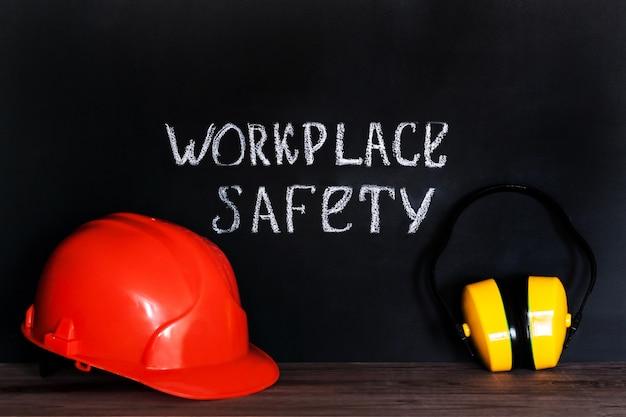 Kask budowlany na czarnym tle z napisem bezpieczeństwa pracy