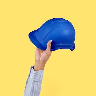 Kask inżyniera trzymany przez ręczną pracę i kampania kariery