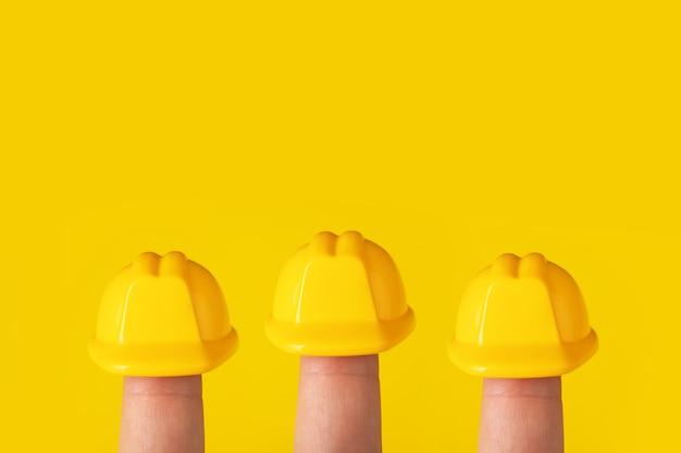 Kask na palcach na żółtym tle, pracownicy budowlani w kaskach ochronnych w pracy at