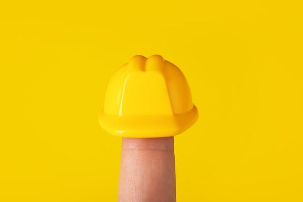 Kask na palcu na żółtym tle, kask budowy na głowę
