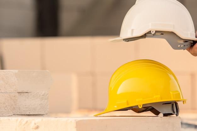 Kask na tle budowy witryny, bezpieczeństwo kasku, święto pracy