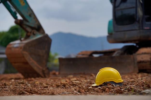 Kask ochronny na placu budowy, tło budowy drogi, koncepcja bezpieczeństwa