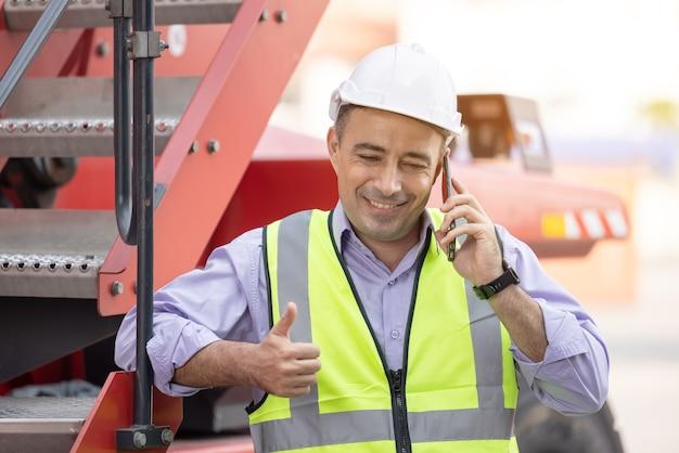 Kask pracownika stojąc i rozmawiając przez telefon komórkowy w stoczni transportowej kontenerów logistycznych