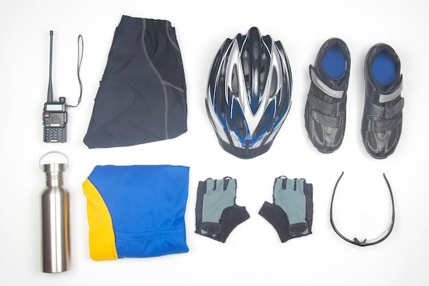 Kask rowerowy, okulary, rękawiczki, butelka, walkie-talkie, odzież sportowa i buty rowerowe na białym