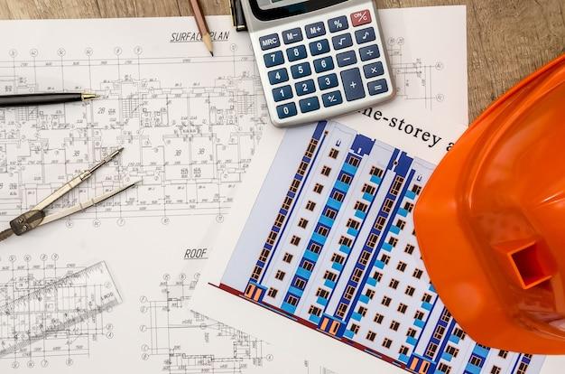 Kask z planami i linijkami, długopis, kalkulator na biurku