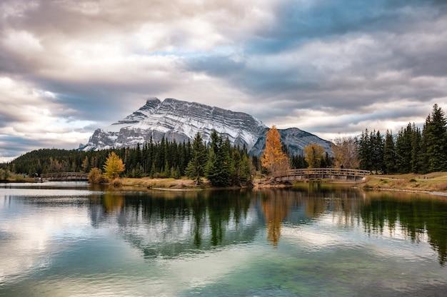 Kaskadowe stawy z górą rundle i drewnianym mostem w jesiennym lesie w parku narodowym banff, kanada