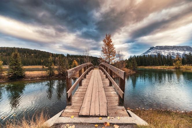 Kaskadowe stawy z mount rundle i drewnianym mostem w jesiennym lesie w parku narodowym banff, kanada. dranatyczny ton