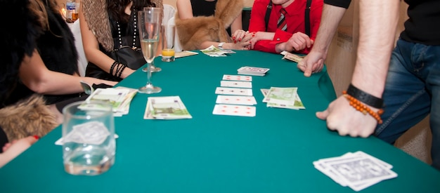 Kasyno domowe. mężczyźni i kobiety grają w karty. stawiaj zakłady z pieniędzmi i żetonami na numery. zielony płótno stołu. gry hazardowe dla dorosłych. gra w pokera, blackjacka. pula