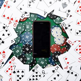 Kasyno online, kasyno mobilne, telefon komórkowy, karty z żetonami na zielonym tle. gry hazardowe. widok z góry.