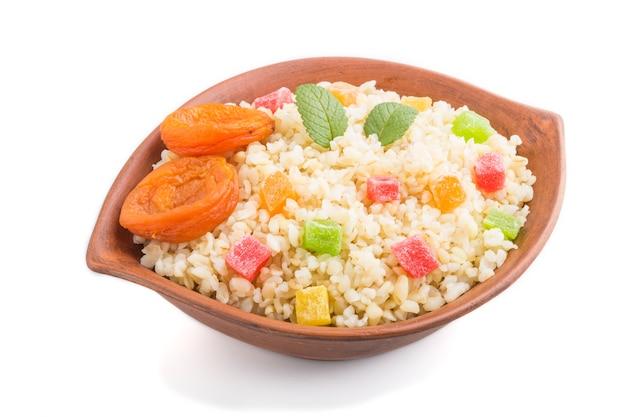 Kasza bulgur z suszonymi morelami i kandyzowanymi owocami w glinianej misce na białym tle. widok z boku, z bliska. tradycyjna kuchnia turecka.