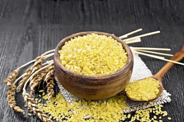 Kasza bulgur - ziarna pszenicy gotowane na parze - w glinianej misce i łyżką na worku, kłosy pszenicy na tle ciemnej drewnianej deski