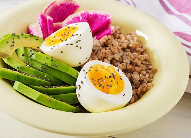 Kasza gryczana buddy miski z awokado, jajka na twardo i arbuz rzodkiewki na białym stole. zdrowe śniadanie.