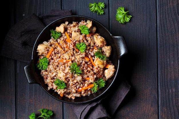 Kasza gryczana pieczona z mięsem kurczaka i warzywami na czarnej patelni, widok z góry, ciemne tło.