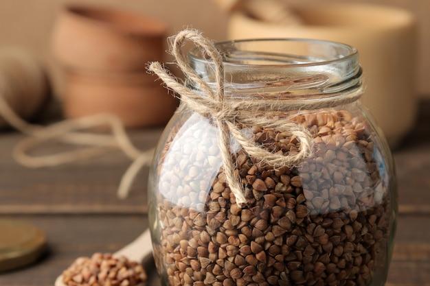 Kasza gryczana sucha w szklanym słoju na pierwszym planie na drewnianym stole brązowym. płatki. zdrowe jedzenie. owsianka.