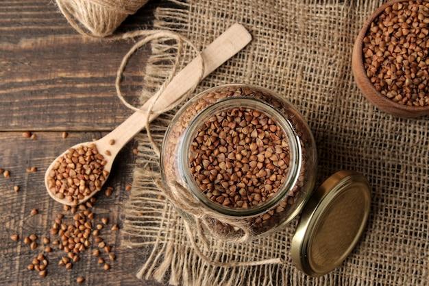 Kasza gryczana sucha w szklanym słoju z drewnianą łyżką. widok z góry na drewnianym brązowym stole. płatki. zdrowe jedzenie. owsianka.