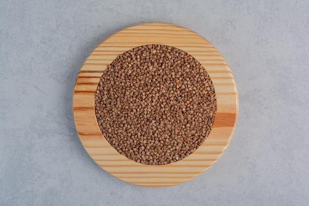 Kasza gryczana ułożona na drewnianym talerzu na marmurowej powierzchni
