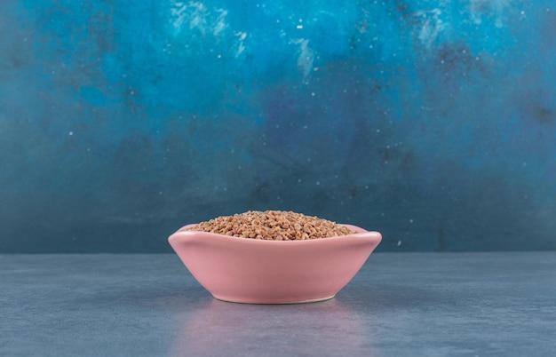 Kasza gryczana ułożona w różowej misce na niebiesko