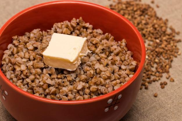 Kasza gryczana w czerwonej misce. zdrowe jedzenie. kasza gryczana i masło.
