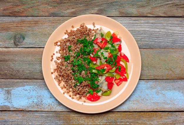 Kasza gryczana z dodatkami rybiego błękitka zapiekana z warzywami, pomidorami, papryką i cebulą na drewnianym tle, zbliżenie z góry