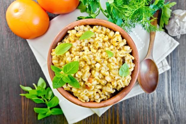 Kasza jęczmienna w glinianej misce z bazylią na serwetce, pomidorami, pietruszką i czosnkiem na tle desek na wierzchu