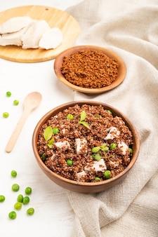 Kasza komosa ryżowa z zielonym groszkiem i kurczakiem w drewnianej misce na białym drewnianym stole i lnianej tkaninie. widok z boku, z bliska.