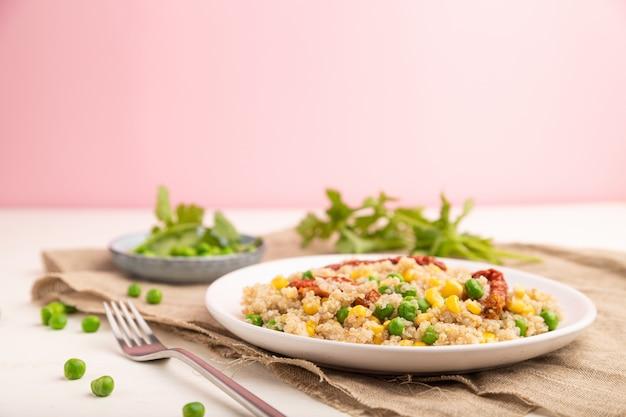 Kasza komosa ryżowa z zielonym groszkiem, kukurydzą i suszonymi pomidorami na talerzu ceramicznym na biało-różowym stole