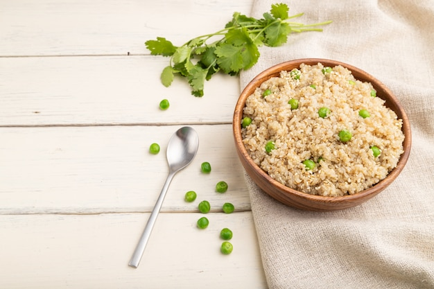 Kasza komosa ryżowa z zielonym groszkiem w drewnianej misce na białym drewnianym stole i lnianej tkaninie. widok z boku, z bliska, kopia przestrzeń.