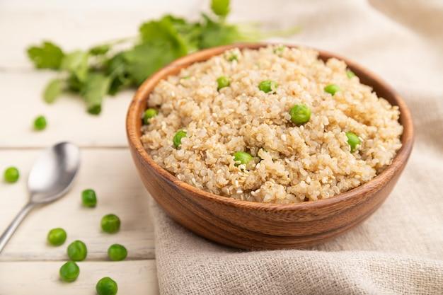 Kasza komosa ryżowa z zielonym groszkiem w drewnianej misce na białym drewnianym stole selektywnej ostrości.