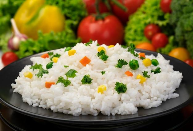 Kasza ryżowa gotowana, podawana z ziołami i warzywami na czarnym talerzu