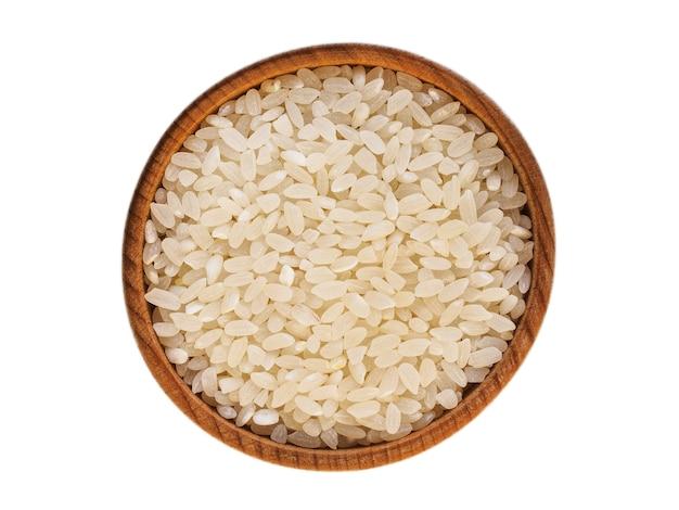 Kasza ryżowa w drewnianym kubku na białym tle na białym tle
