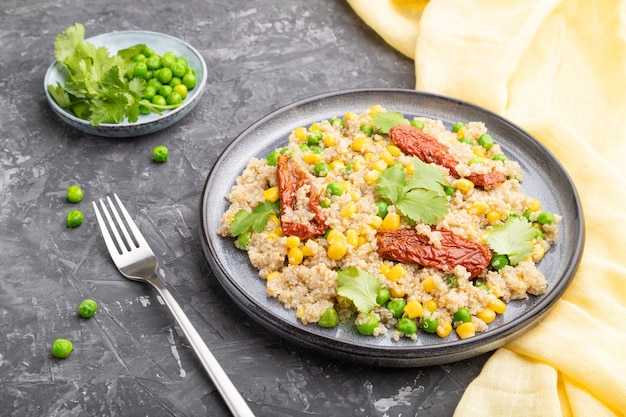 Kasza z komosy ryżowej z zielonym groszkiem, kukurydzą i suszonymi pomidorami na talerzu ceramicznym na szarej betonowej powierzchni i żółtej tkaninie