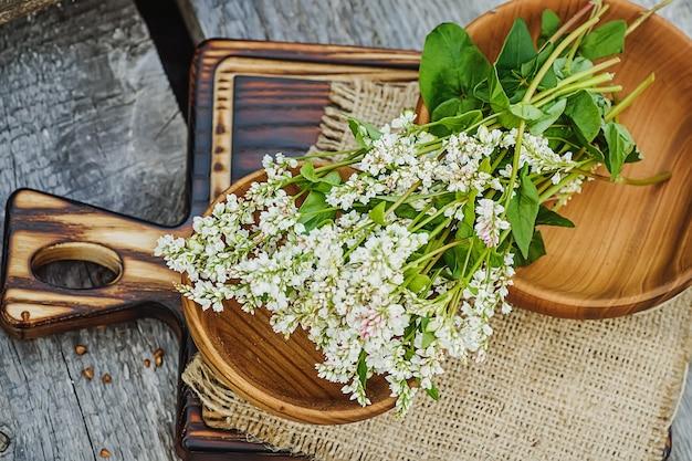 Kaszę gryczaną suszyć na drewnianym talerzu. pokarm dla surowej żywności i wegan. składnik zdrowej żywności odchudzającej.