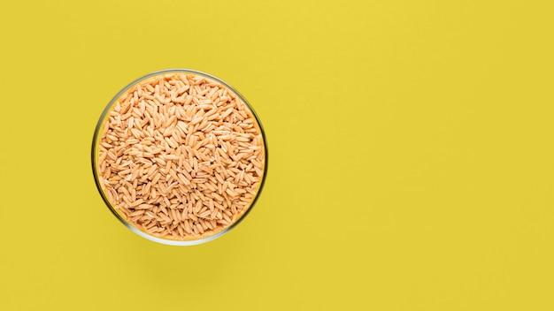 Kasze owsiane w szklanej misce na żółtym tle, surowe całe nasiona owsiane