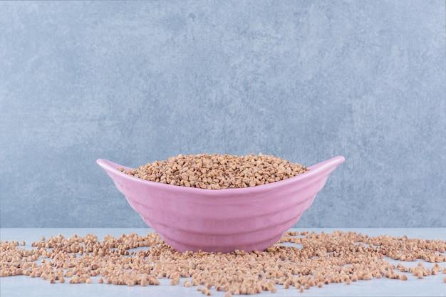 Kasze rozsypane, a pośrodku na marmurowej powierzchni leży pełna, różowa miska kaszy gryczanej