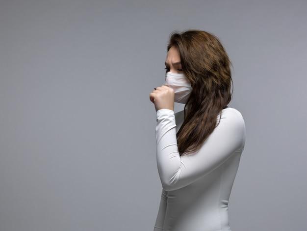 Kaszel dziewczyna zakrywa usta w białej masce ochronnej