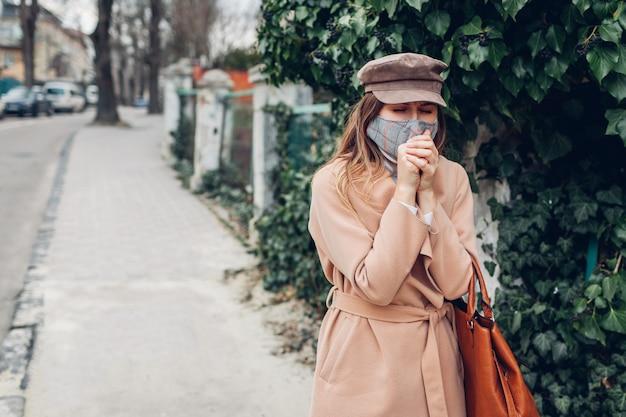 Kaszel kobiety nosi maskę wielokrotnego użytku na zewnątrz podczas pandemii koronawirusa covid-19. kobieta mdłości. trzymać dystans