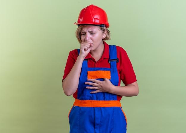 Kaszląca młoda kobieta budowlana w mundurze odizolowana na oliwkowozielonej ścianie