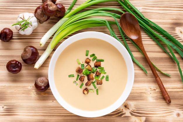 Kasztanowa tradycyjna zupa krem na drewnianym stole. widok z góry.