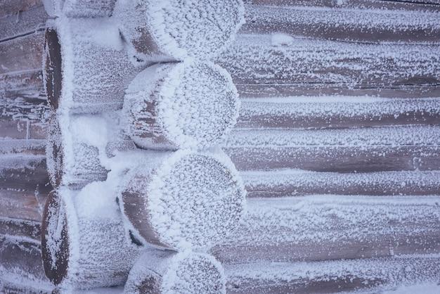 Kąt domu z bali w mrozie. zima w górskiej wiosce. tonowanie kolorów. niski kontrast