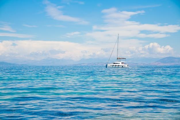 Katamaran przy błękitnym morzem. żaglówka katamaran na oceanie w pobliżu plaży.