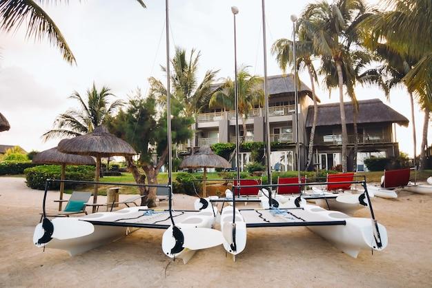 Katamarany z żaglami stoją na plaży przed willą na tropikalnej wyspie mauritius.