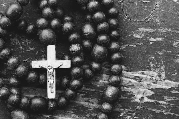 Katolicka modlitwa różańcowa z krzyżem na starym czarnym drewnianym z miejscem na tekst. zbliżenie, widok z góry. czarno-biały stonowany