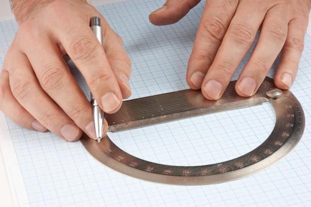 Kątomierz w ręku na papierze milimetrowym