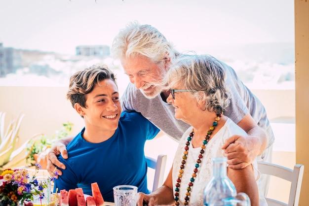 Kaukascy ludzie w różnym wieku i pokoleniach - dziadkowie i wnuk razem rodzina przy stole jedząc jedzenie i ciesząc się przyjaźnią - szczęśliwe stare i młode piękne osoby