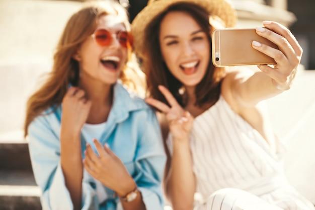 Kaukascy młodzi przyjaciele z naturalnym makijażem bierze selfie