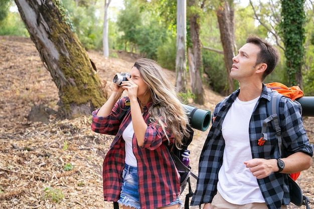 Kaukascy wędrowcy fotografujący, spacerujący lub trekking po leśnej ścieżce otoczonej drzewami. ładna kobieta trzyma aparat, strzelanie i wędrówki z przystojnym mężczyzną. koncepcja turystyki, przygody i wakacji