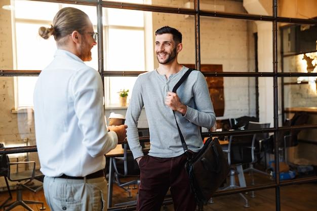 Kaukascy zadowoleni koledzy rozmawiają i uśmiechają się stojąc w nowoczesnym biurze