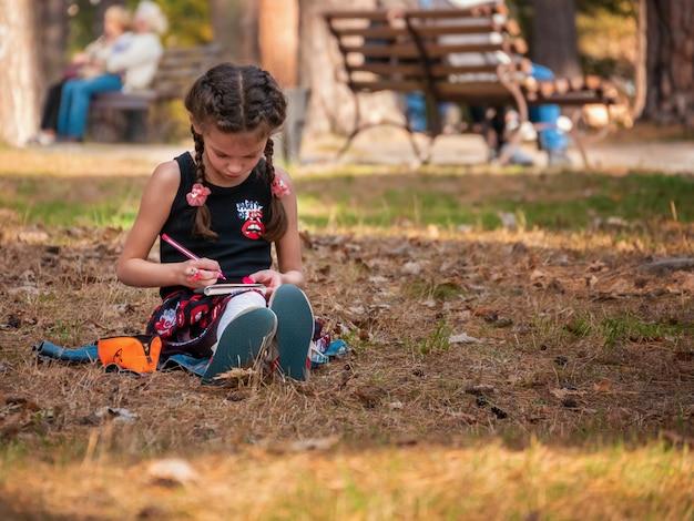 Kaukaska 6 lat dziewczyna maluje na zewnątrz koncepcja sama utalentowana edukacja dzieci