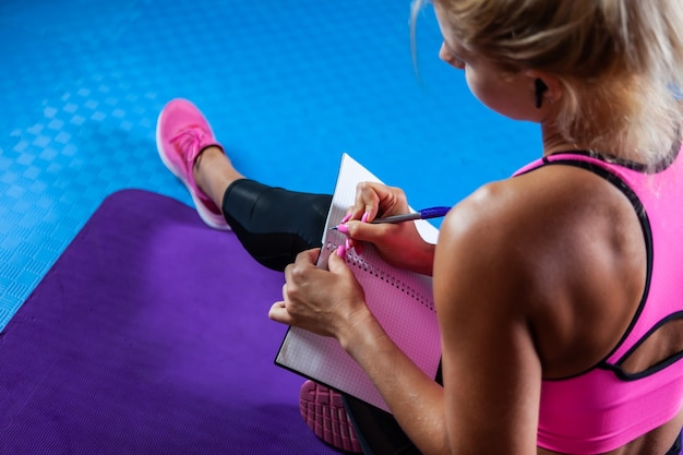 Kaukaska blond fitness kobieta zastanawia się i zapisuje w zeszycie treningowym plan treningu, siedząc na macie w klasie fitness. widok z tyłu